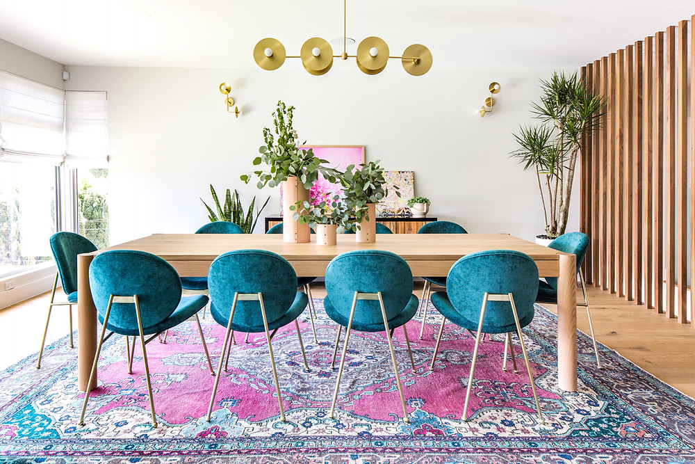 View of dining room with blue chairs and pink rug