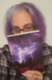 Author and Book.  Image of Nicola Noble h9olding a copy of Just ike Lightning.  Her hair colour matches the stormy sky on the book cover.