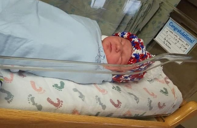 Photo of Link.  He's wearing a crocheted hat and is swaddled, cozy, and sleeping in the clear hospital bassinet.