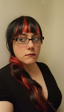 Author's headshot.  Her hair is black with large red streaks.  It's braided and over her right shoulder.  She's wearing glasses.