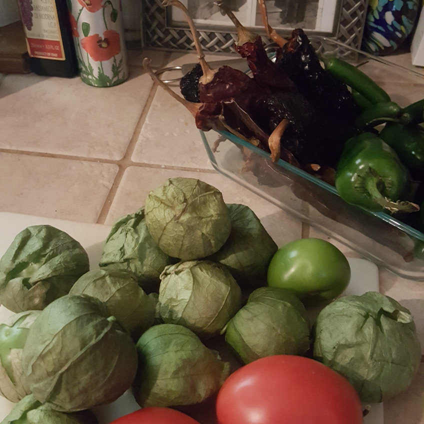 Photo.  in the foreground is a small white cutting board topped with Roma tomatoes and tomatillos still in their leafy wrappers.  To the side is a small, rectangular pyrex dish filled with jalapenos, serranos, and dried ancho & guajillo chiles