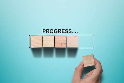 A hand places a wooden block in a box of other box that resembles a computer loading bar. above is written progress.