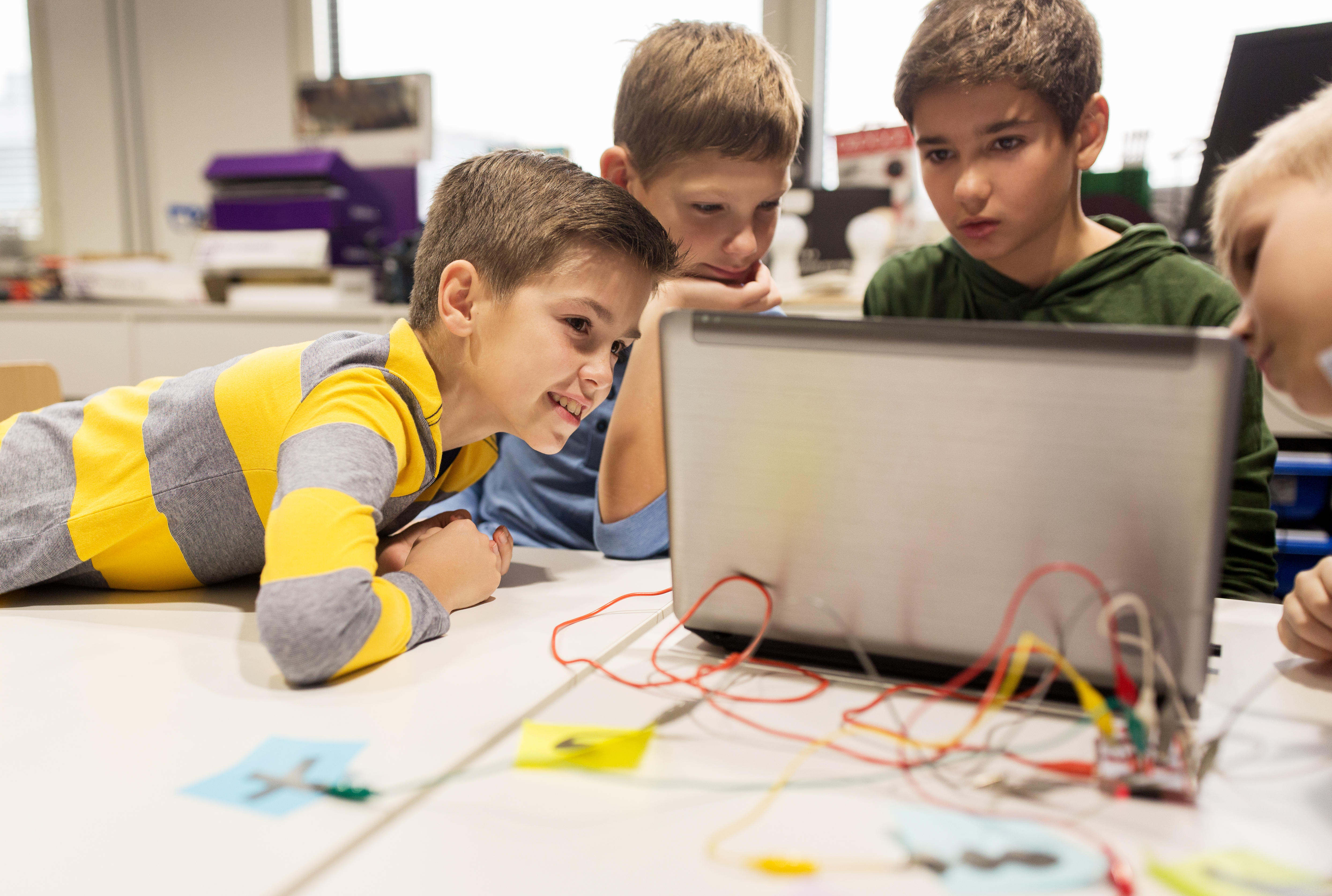 education, children, technology, science and people concept - group of happy kids with laptop comput
