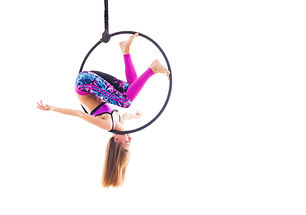 Woman hanging in aerial ring, isolated o