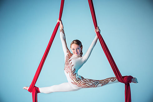 Graceful gymnast performing aerial exerc