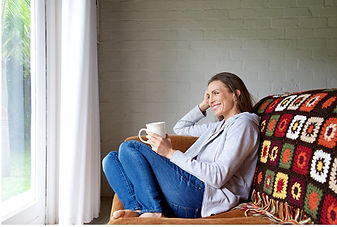 A lady sits on a sofa holding a mug.