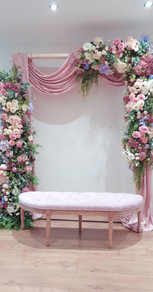 Wooden arbour backdrop with draping and flowers