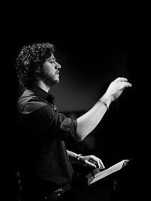 Adam Kleinberg conducting an orchestra