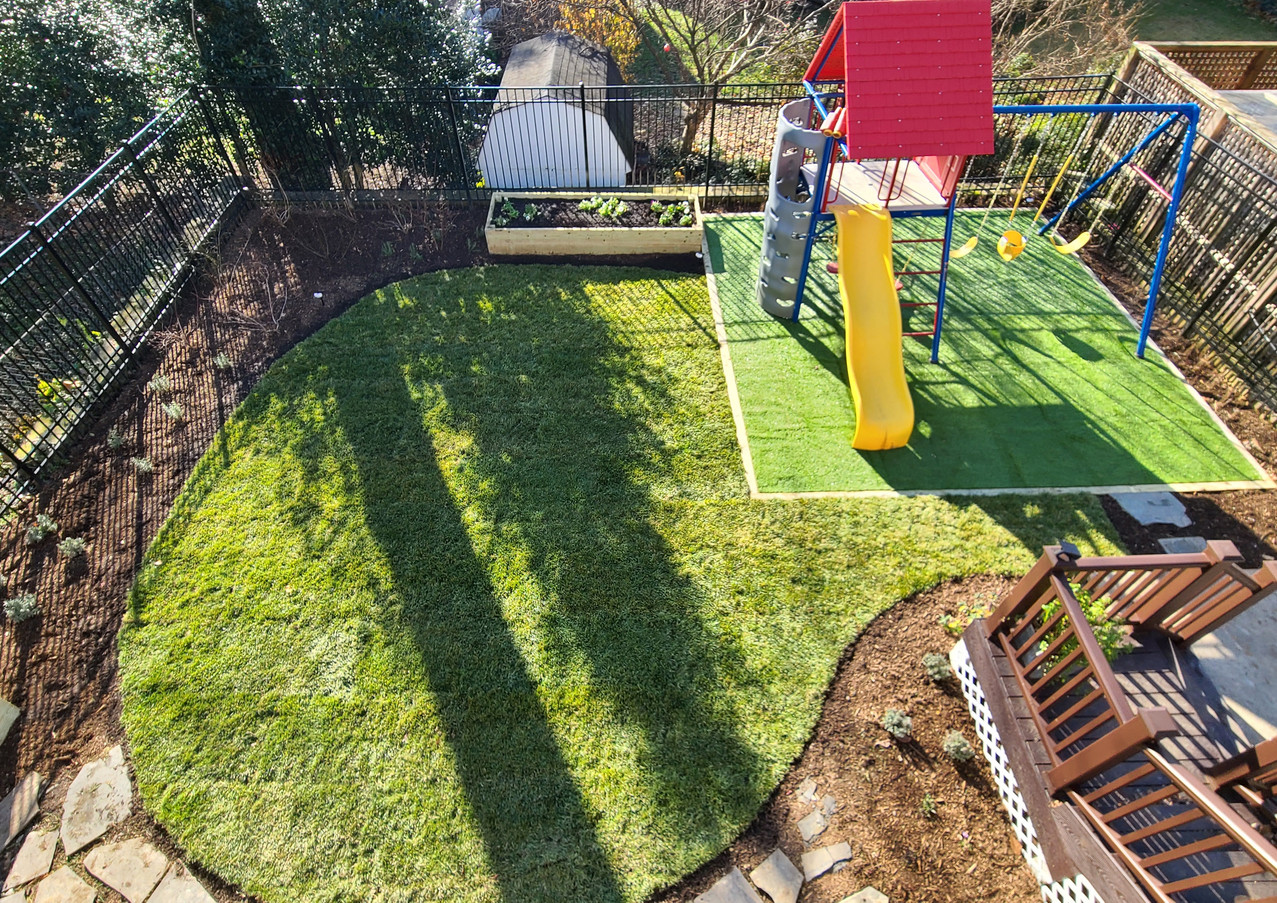 Newly installed backyard landscape features playset area, edibles landscape and new sod