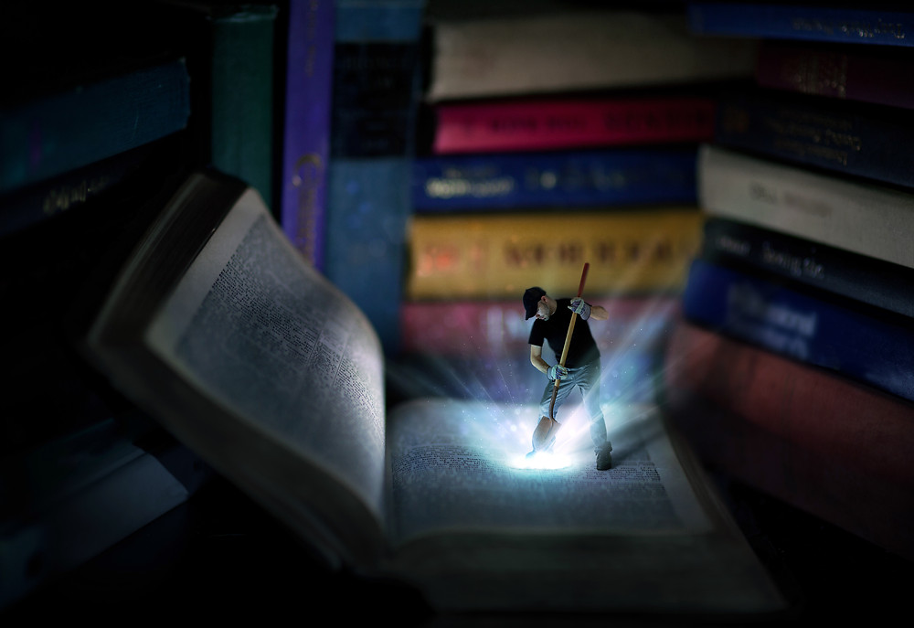 Man stands on giant book and shovels out light