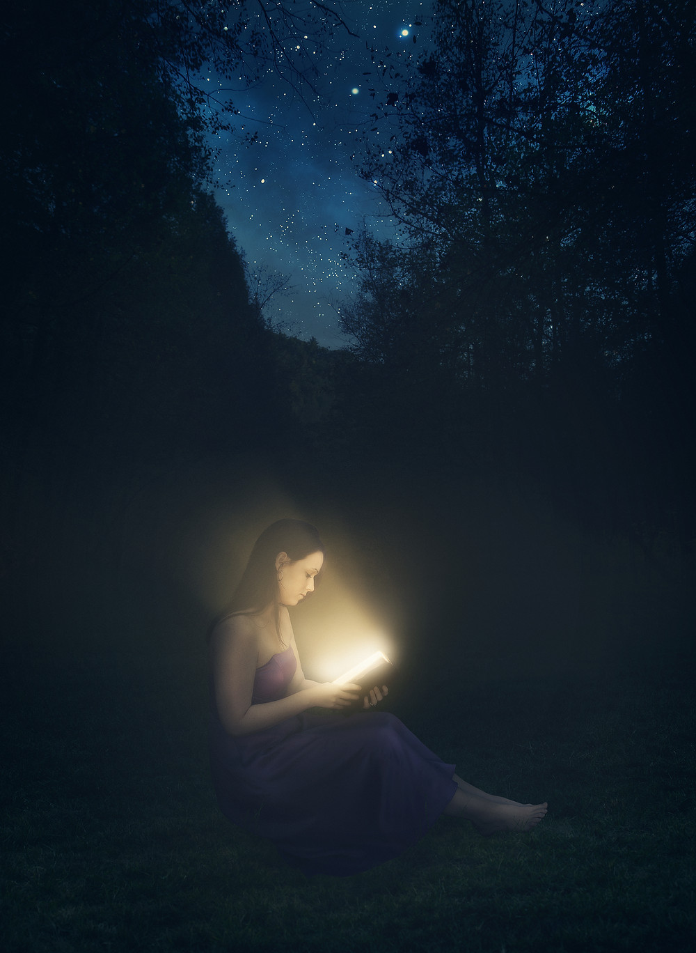 Woman sits outside at night, reading a book that shines light on her