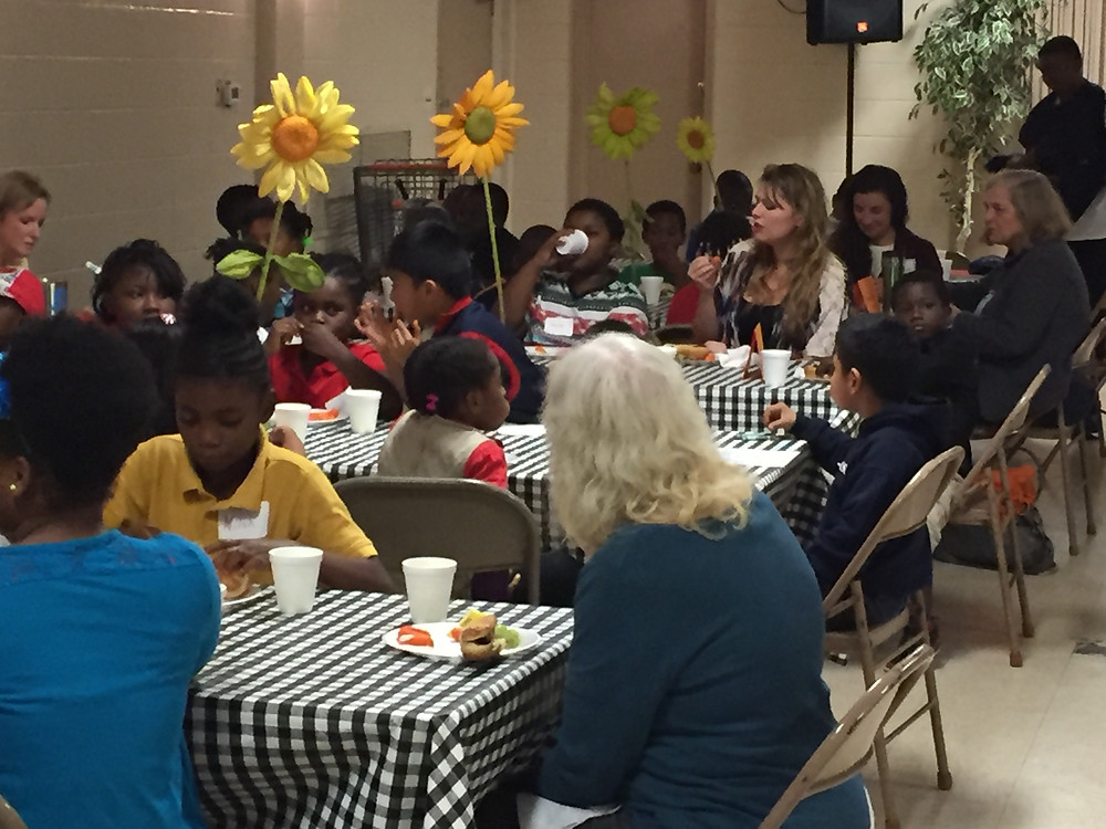 FirstWorks students gather with teachers for dinner.