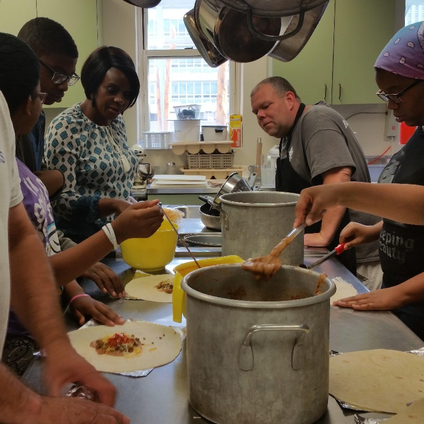Youth and adult volunteers from UsMIH prep burritos at the Carpenter House homeless food ministry.