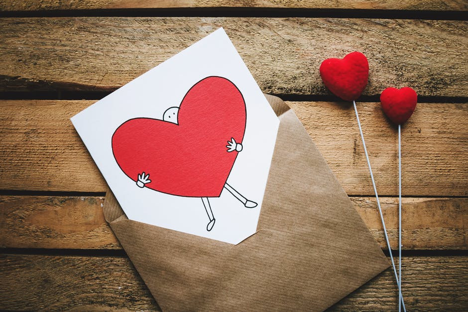 White, Black, and Red Person Carrying Heart Illustration in Brown Envelope