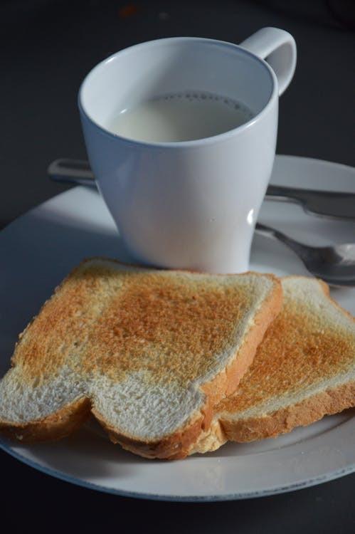 White Ceramic Mug Beside Toasted Bread