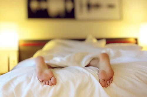 Person Lying on Bed Covering White Blanket
