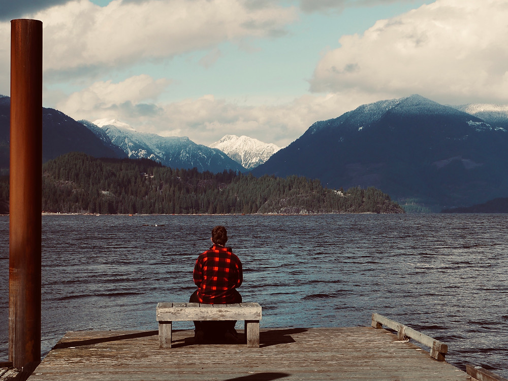 man staring out across the water at some gorgeous snow covered mountains