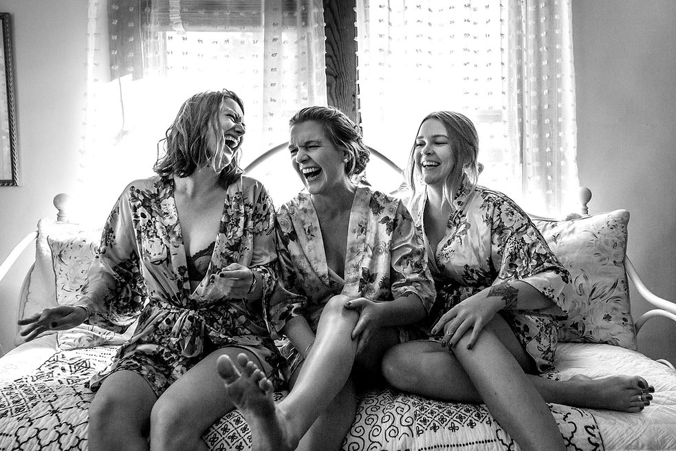 Bride and Bridesmaids on Bed Getting Rea