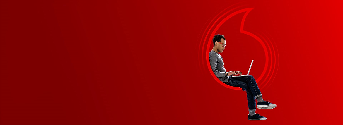 man sitting in a vodafone logo wearing a grey jumper and glasses whilst on his laptop