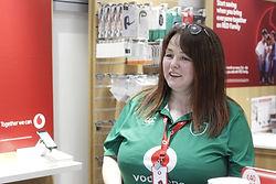 Vodafone Retail staff member smiling in vodafone store wearing a green vodafone uniform