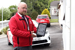 Fots team memeber showing offers to customer on his ipad and weaing red vodafone uniform