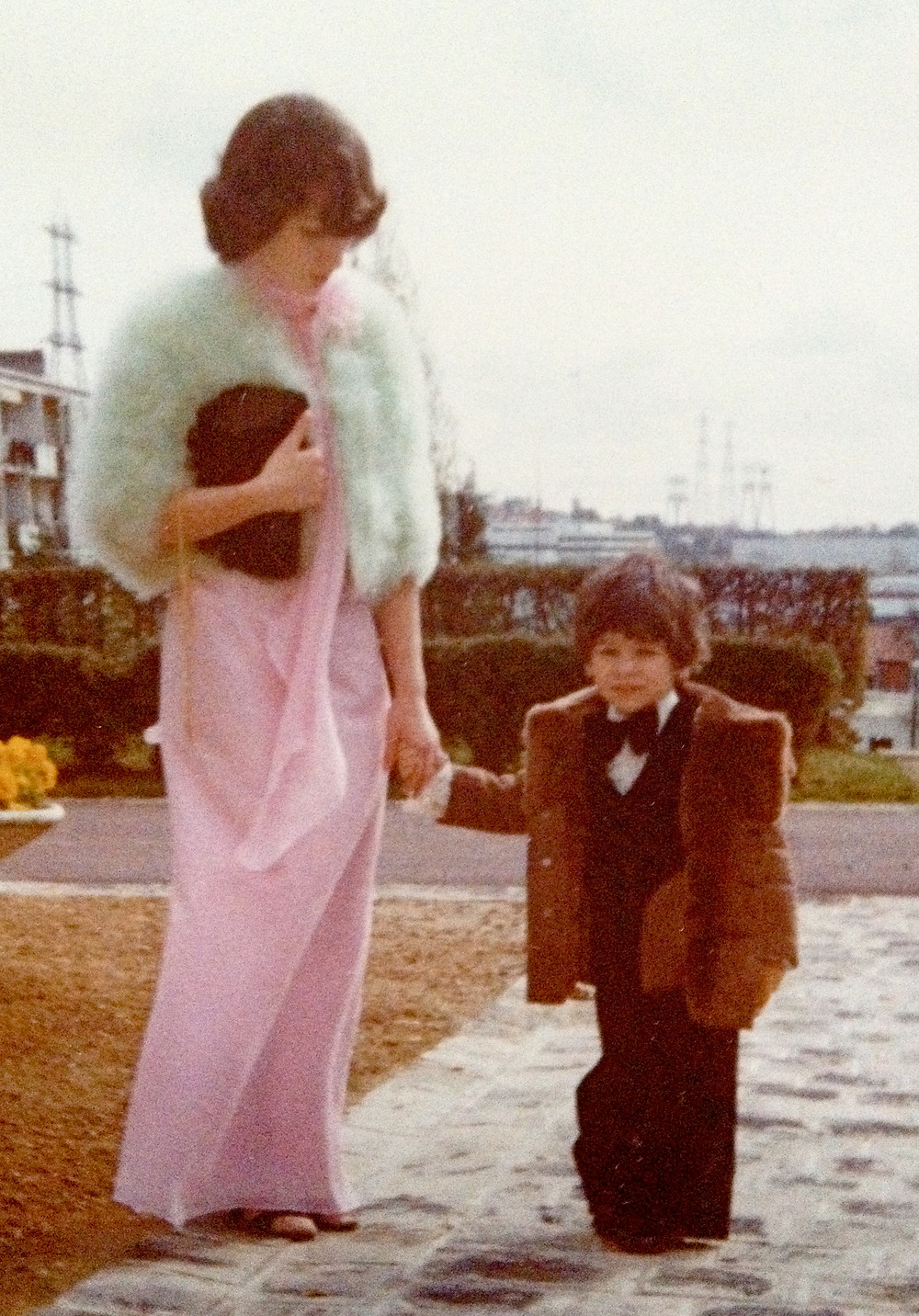 A photo of a young mom and her son. It's an older photo. The mom wears a long pink dress and a white short fur coat. the boy has a little brown fur coat. they are holding hands.
