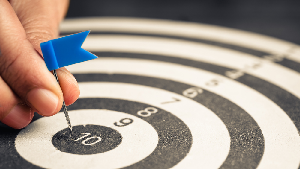 A flag pin is placed at the center of a target, representing achieving your goals when goal setting.