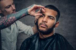 Stylish tattooed barber makes haircut to