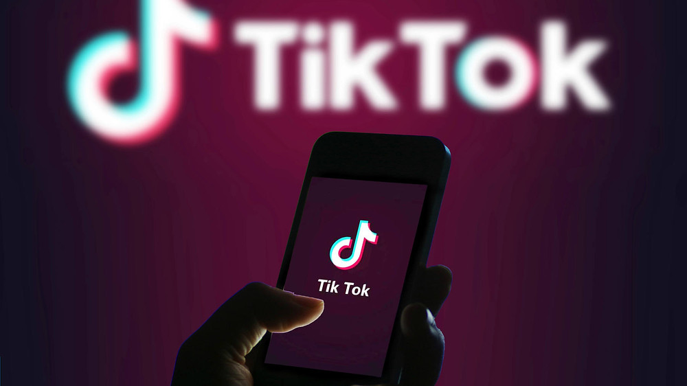 Image of hand holding phone with Tiktok logo