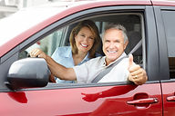 A happy couple in a rental car giving a thumbs up