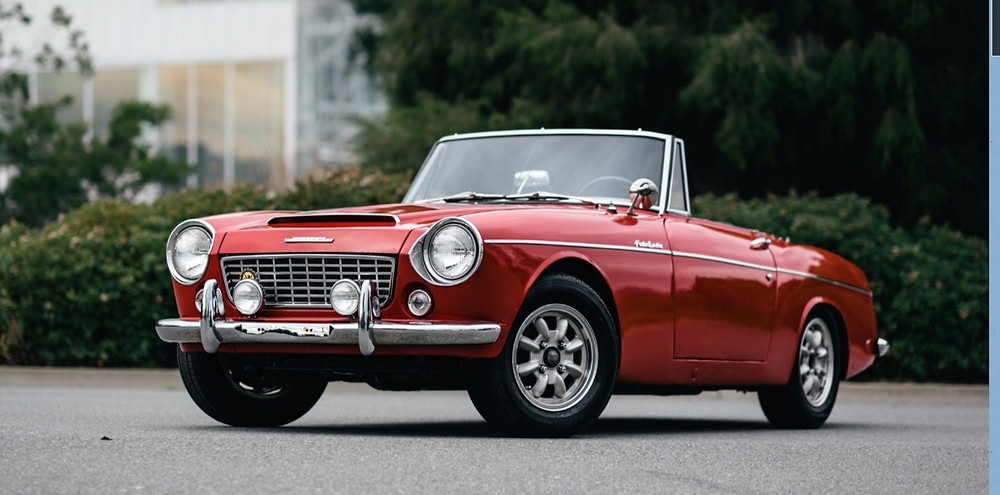 An open top red Datsun Fairlady roadster vintage sports car parked on a leafy drive. Wish I still had mine.