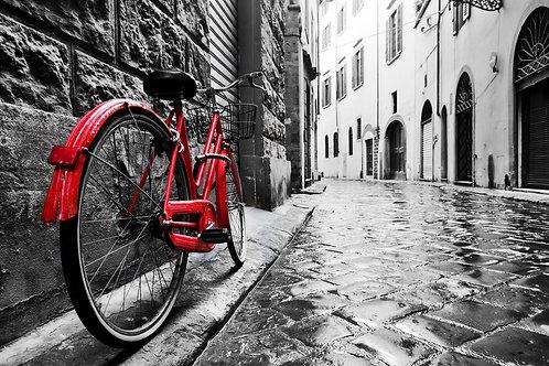 Красный велосипед на мостовой улице в старом черно-белом городе