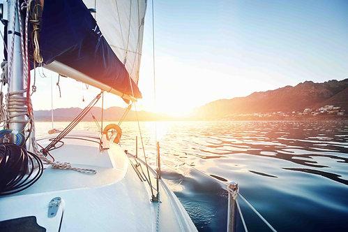Парусная яхта на океанской воде на восходе солнца