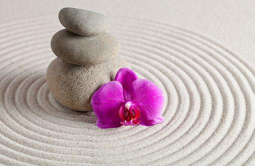 Базальтовые камни и фиолетовый цветок орхидеи на белом песке