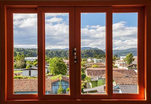 Вид из окна на черепичные крыши домов провинциального городка