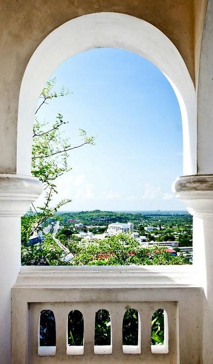 Вид из каменного арочного окна на город