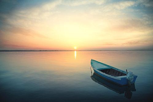 Лодка на спокойной воде на фоне живописного заката