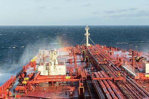 Нос грузового корабля в радужных брызгах морской воды