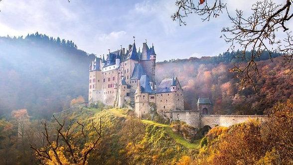 Замок Нойшванштайн в осеннем горном лесу