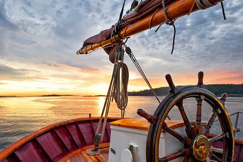 Парусник на фоне восходящего солнца в море