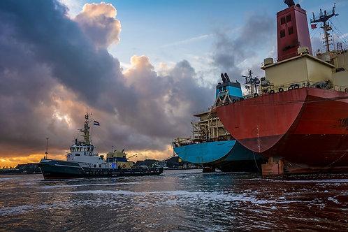 Швартовка торговых судов на фоне красочных облаков