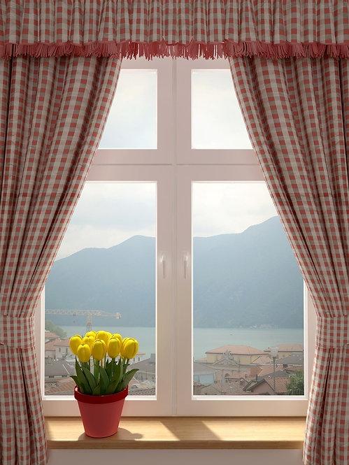 Вид из окна со шторами и желтыми тюльпанами на старый городок у моря