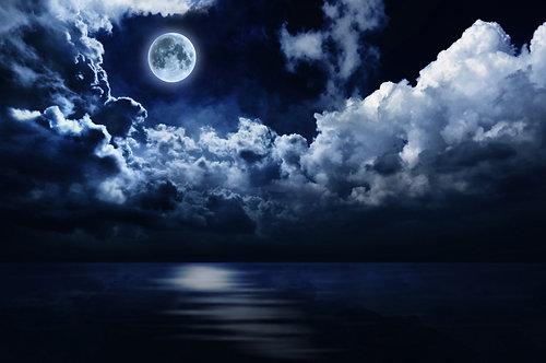 Полная луна в облачном ночном небе над водой