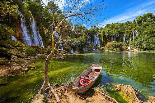 Старая лодка на фоне водопада Кравице в Боснии и Герцеговине