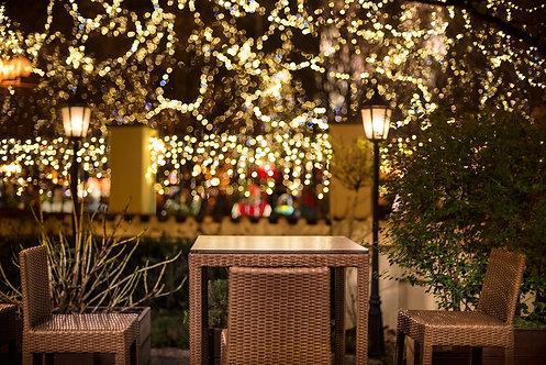Уличное кафе в ночное время на фоне городских огней