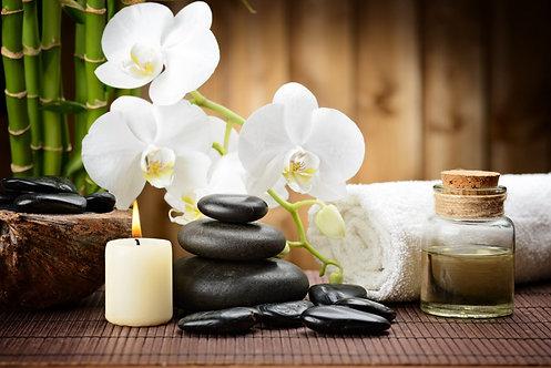 Черные базальтовые камни и ветка с белыми цветами орхидеи