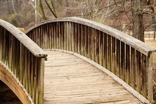 Старый деревянный мост над небольшим ручьем в парке