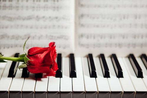 Красная роза на клавишах пианино и музыкальные ноты