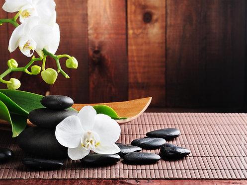 Ветка с белыми цветами орхидеи и черные базальтовые камни