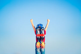 Kid with jetpack against blue sky. Child